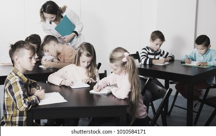 Positive little boys and girls with teacher drawing in classroom