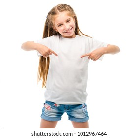 Positive little girl in casual white T-shirt indicates at blank space for logo design