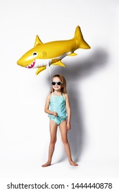positive little girl dressed in a swimsuit, wears a balloon in the shape of a yellow shark fish, celebrates the holiday, against a light background. The concept of children and recreation