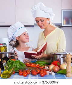 Positive little girl helping mother to prepare vegetables at home