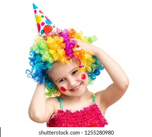 Positive little girl poses holding her head in colorful clown wig isolated on white background