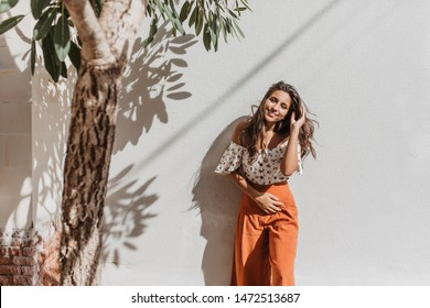 Positive long-haired lady in orange summer pants with smile looks into camera on white background with olive tree