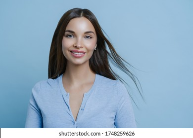 Positive lovely feminine lady happy to have first date with boyfriend, smiles broadly, has appealing appearance, glad to hear something pleasant, models indoor alone, wears blue casual jumper