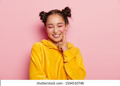 Positive lovely woman with pinup makeup, keeps index finger on cheeks, has eyes closed, dreams about something pleasant, wears yellow velvet hoody, models against pink background. Natural beauty