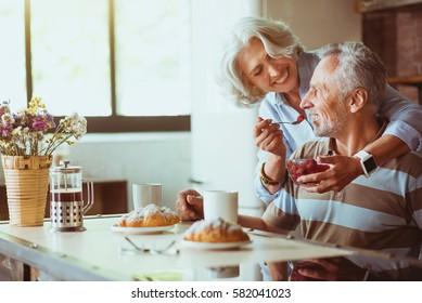 Positive loving aged coupel having breakfast