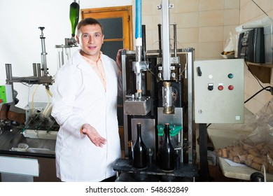positive male assembly line operator working in modern wine factory