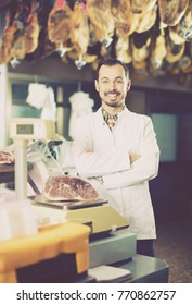 Positive male assistant using scales in butcher`s shop