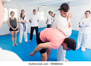 Positive male coach explaining painful hold to adults in taekwondo class