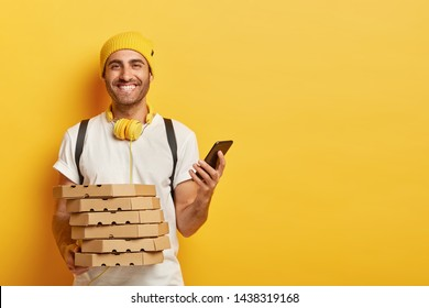 Positive male customer gets pizza boxes, uses smart phone for online order, has toothy smile, going to have tasty snack, dressed in casual white t shirt, isolated on yellow wall, checks delivery