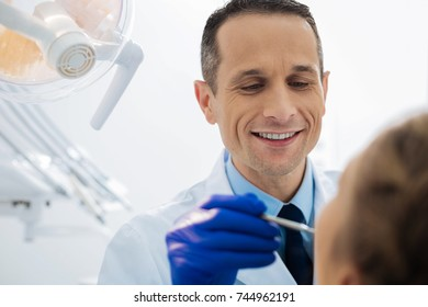Positive male dentist working with a patient