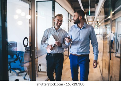 Positive male entrepreneurs in smart casual wear strolling in office using technology talking to each other, smiling prosperous men business partners satisfied with cooperation and meeting in office