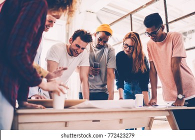 Positive male and female architects working in collaboration discussing ideas and satisfied with productive job,professional group of designers drafting project pondering on sketch and successful plan