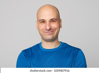 Positive male with funny expression. Man dressed casually. Bald guy smiling isolated on gray studio background