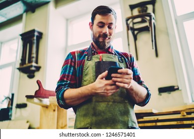 Positive male joiner in apron for safety on work satisfied with good feedback about his manufacture business in networks using mobile phone and 4G connections, smiling bearded maker holding cellular