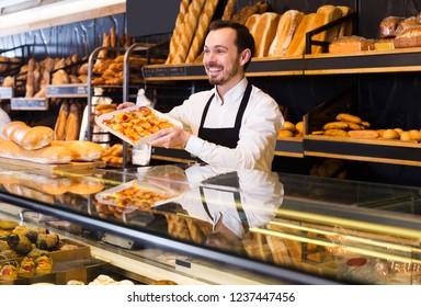 Positive male seller offering fresh tasty bun in bakery