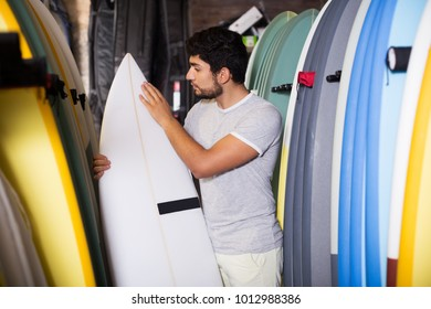 positive male surfer holding professional surfboard in the shop for surfing