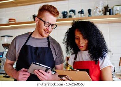 Positive male waiter and female waitress checking offering standing in coffee shop.Young man and woman in red aprons making cost plan of own cafeteria interior.Concept of partnership