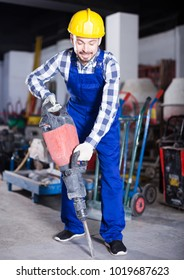 Positive male worker starting to work with demolition hammer at workshop