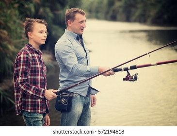Positive man and boy fishing together on freshwater lake from shore