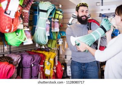 Positive man choosing alpinism equipment in sports equipment store