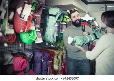 Positive man choosing climbing equipment in sports equipment store