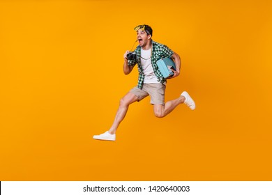 Positive man with diving mask on his head takes pictures with retro camera. Guy in shorts and green shirt jumping with suitcase on orange background