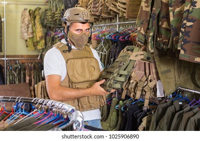 positive man with flak jacket in hands in airsoft market