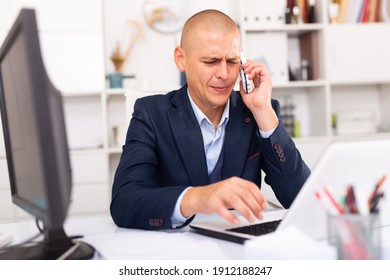 Positive man in formalwear talking on mobile phone at company office