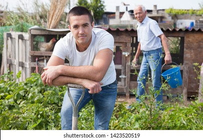 Positive man  horticulturist with garden shovel at  land in  garden, during harvesting with family