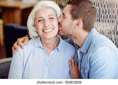 Positive man kissing his grandmother