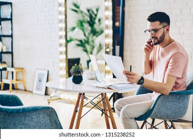 Positive man in optical eyewear working remotely with paper documents calling to colleague for consultancy about finance side using 4g internet on modern smartphone gadget sitting at home table
