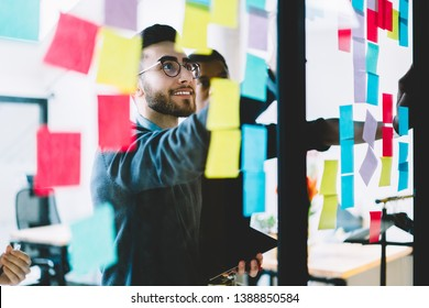 Positive man in optical spectacles with cute smile on face making notes on paper sticks during collaboration with colleagues, happy crew of professional people searching ideas for startup project