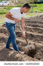 Positive man  professional horticulturist with garden shovel at  land in  garden