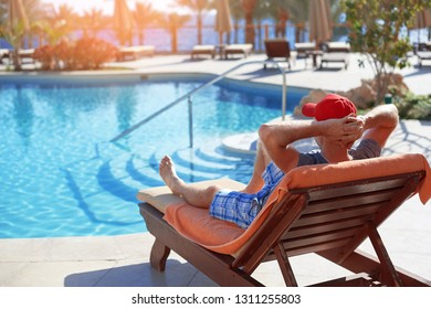 Positive man in red hat resting near the swimming pool hotel in Egypt. Concept beautiful lifestyle
