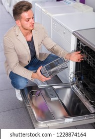 positive man selecting modern dishwasher in hypermarket and smiling