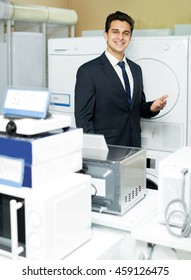 Positive man seller at household appliances section of supermarket