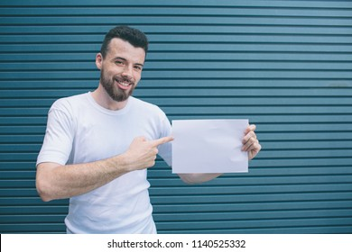 Positive man is standing and holding white piece of paper in left hand and pointing with finger on right one. Guy is looking on camer and smiling. Isolated on striped and blue background.