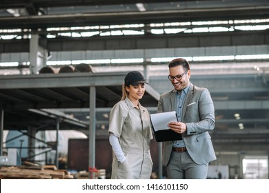 Positive manager and employee talking at manufacturing factory.