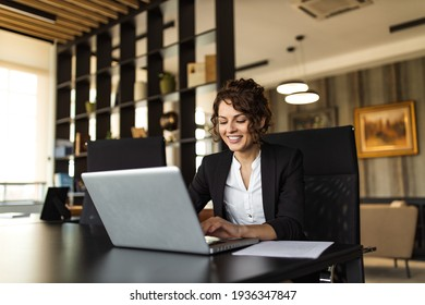 Positive manager using laptop in the office, portrait. Sitting at desk in luxurious office.