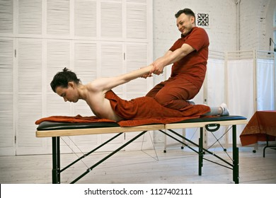Positive manual therapist pulling back caucasian male patient. Horizontal sideview shot