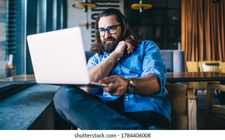 Positive mature 40 years male in spectacles for vision protection watching video on laptop computer on free time, smiling prosperous businessman reading news about online project work remotely