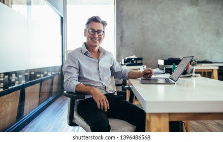 Positive mature businessman sitting at office desk. Mid adult caucasian male executive at work.