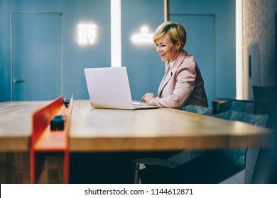 Positive mature coach laughing during watching business webinar online on modern laptop connected to wireless 4G internet.Cheerful female entrepreneur 50 years old reading funny news on netbook