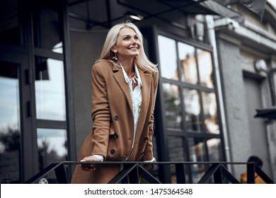 Positive mature lady smiling and leaning on the banister outdoors