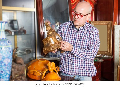 positive mature man  shop of antique goods in search of interesting objects