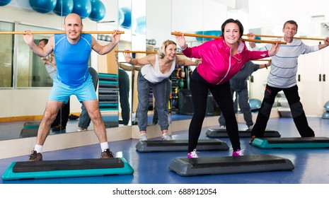 Positive mature people do aerobics  in a sport club