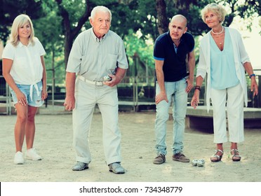 Positive mature people friends playing petanque in park outdoor
