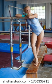 Positive mature woman acrobat in bodysuit exercising gymnastic action at gym
