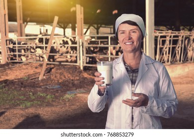 Positive mature woman farmer with cow milk in glass at cowshed on dairy farm