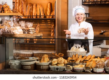 Positive mature woman selling fresh pastry and baguettes in local bakery